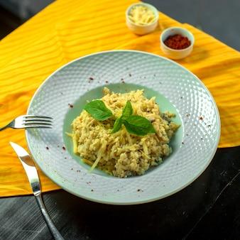 Вид сверху овощного салата с грибами грецкими орехами и сыром, подается со сливочным соусом в белой тарелке
