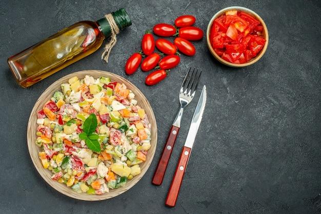 濃い灰色の背景の側面にトマトオイルボトルとカトラリーと野菜サラダの上面図