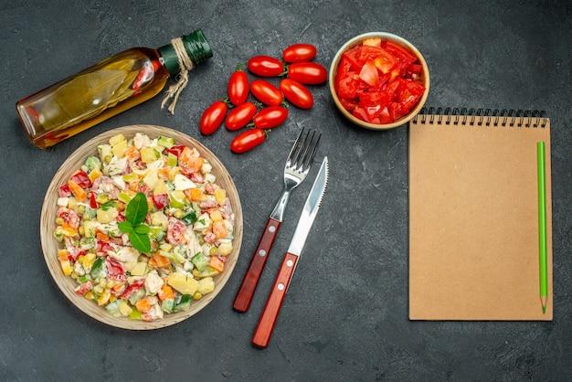 濃い灰色の背景の側面にトマトオイルボトルカトラリーとメモ帳と野菜サラダの上面図