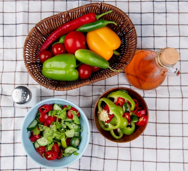 Вид сверху овощные салаты в мисках и овощи в корзине как перец помидор огурец с солью и маслом на фоне плед ткани
