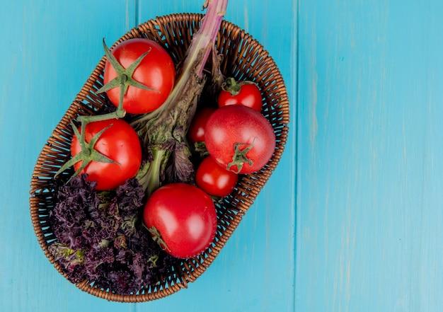 コピースペースを持つ青い表面にバスケットにバジルとトマトとして野菜のトップビュー