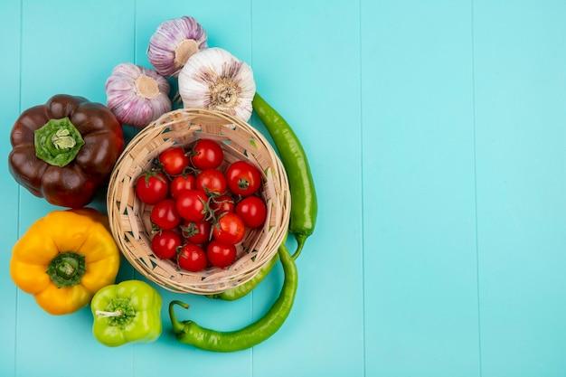 파란색 표면에 토마토와 오이 고추 마늘 바구니로 야채의 상위 뷰