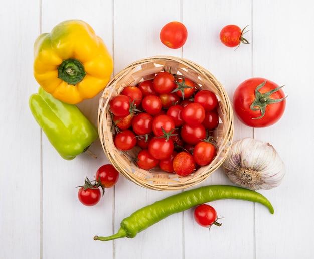 コショウニンニクの球根とトマトの木製の表面の周りのトマトのバスケットとして野菜のトップビュー