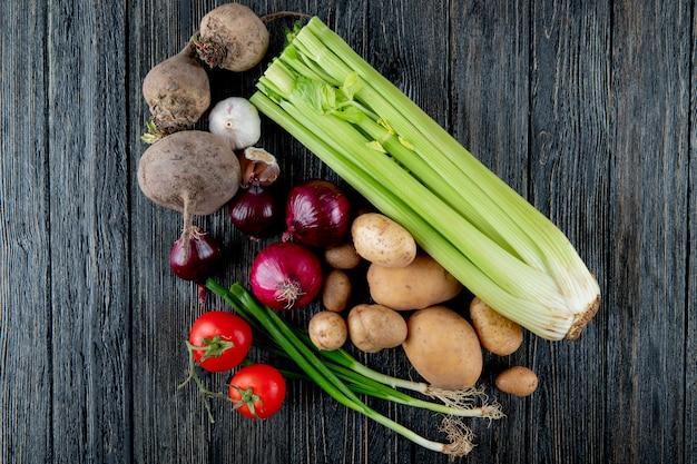コピースペースを持つ木製の背景にセロリビートの根ニンニクタマネギトマトとネギとして野菜のトップビュー