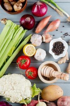 木製の背景にセロリ玉ねぎトマトカリフラワーとカットレモンとニンニクのクラッシャーと野菜のトップビュー