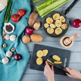 木製の背景にまな板の上のジャガイモを切る女性の手でセロリトマトタマネギニンニク卵として野菜のトップビュー