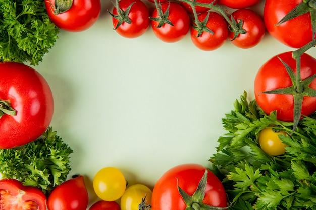 コピースペースを持つ白い表面にコリアンダーとトマトとして野菜のトップビュー
