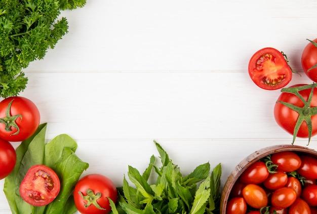 Взгляд сверху овощей как листья мяты зеленого цвета шпината томата кориандра на деревянной поверхности с космосом экземпляра