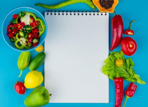 Вид сверху овощей как огурец перец томатный салат с семенами черного перца и нарезанный перец с блокнотом на синей поверхности с копией пространства