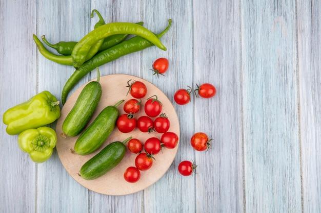 Взгляд сверху овощей как томат огурца на разделочной доске с перцем на деревянной поверхности