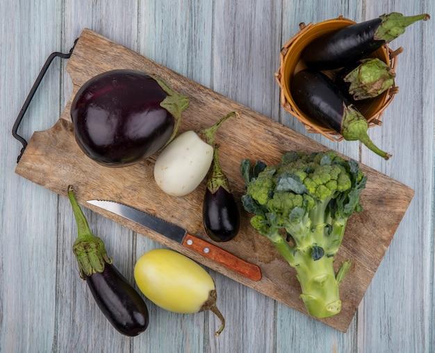 Вид сверху на овощи в виде баклажанов и брокколи с ножом на разделочной доске, в корзине и на деревянном фоне