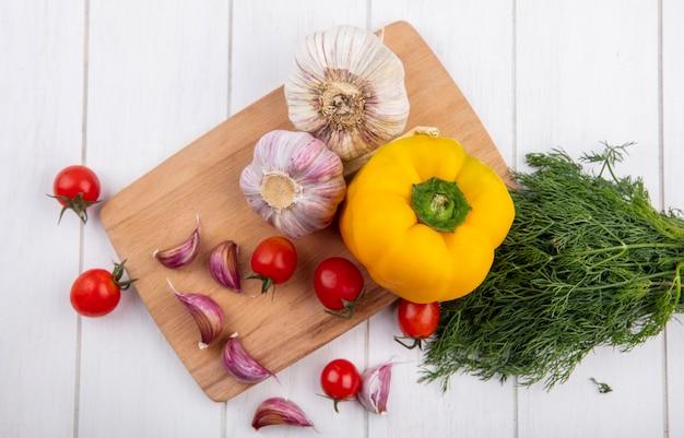 木製の表面にディルとまな板の上のニンニクトマトコショウとして野菜のトップビュー