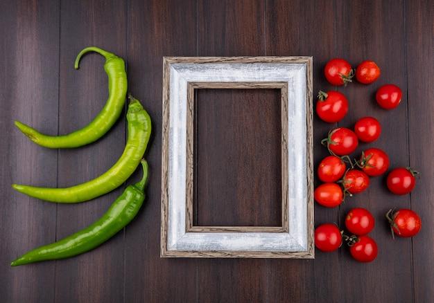 唐辛子と木製の表面上のフレームの周りのトマトとして野菜のトップビュー