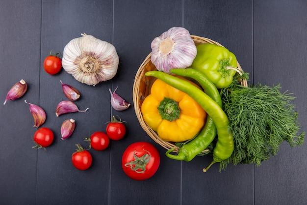 Взгляд сверху овощей как перец укропа чеснока в корзине и зубчиков чеснока томатов на черной поверхности