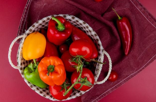 Взгляд сверху овощей как огурец томата перца в корзине на ткани бордо и поверхности бордо