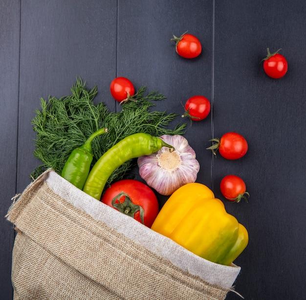 黒の表面に袋からこぼれるペッパートマトガーリックディルとして野菜のトップビュー
