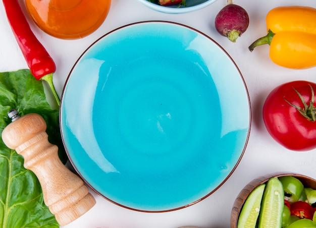 버터와 무 고추 토마토로 야채의 상위 뷰 및 흰색 표면에 빈 접시와 함께 떠나