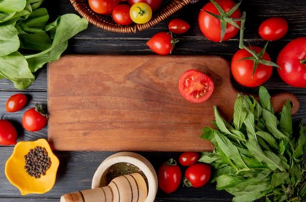 トマトと緑のミントとして野菜の上から見る黒胡椒の種とガーリッククラッシャーの葉し、木の表面にまな板の上のトマトをカット