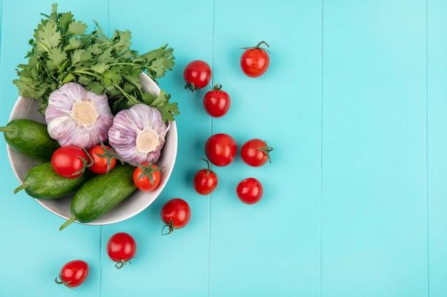 Взгляд сверху овощей как кориандр огурца томата и чеснок в шаре на голубой поверхности