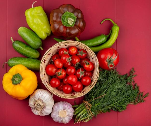 Вид сверху овощей как помидоры в корзине с перцем, чесноком, укропом на красной поверхности