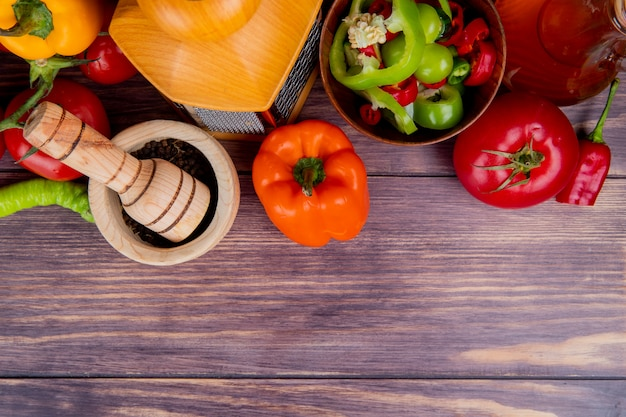 おろし金にんにくクラッシャーと溶かしバターと全体とスライスしたピーマントマト全体のコピースペースと木の上面図