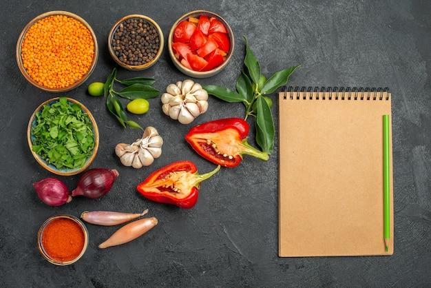 Вид сверху на овощи миска с чечевицей, травами, специями, помидорами, болгарским перцем, тетрадным карандашом