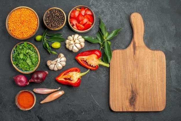 렌즈 콩 허브 향신료 토마토 피망 도마의 야채 그릇의 상위 뷰