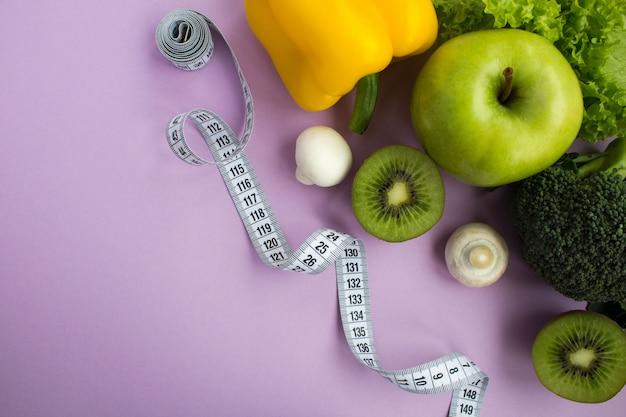 紫の表面に野菜、果物、白いセンチメートルのトップビュー