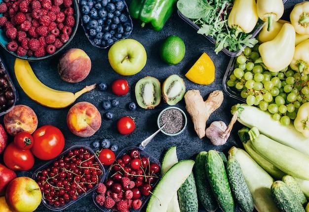 검은 배경에 있는 야채, 과일, 딸기의 상위 뷰가 닫힙니다.
