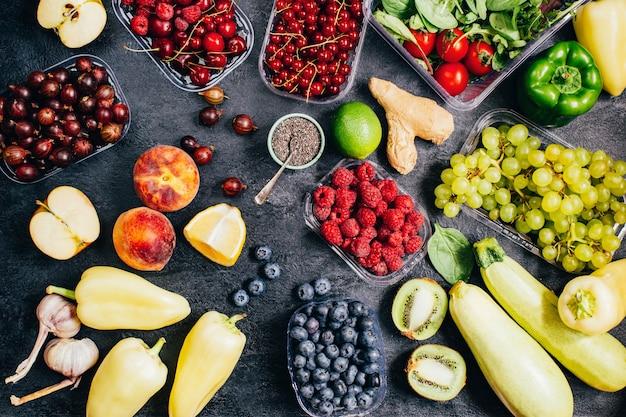 검정색 배경에 있는 야채, 과일, 딸기의 상위 뷰가 닫힙니다.