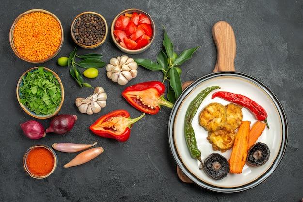 まな板の上の皿の野菜レンズ豆スパイストマトペッパープレートの上面図