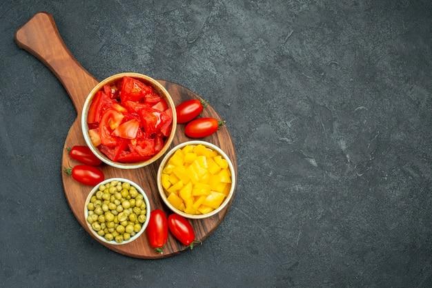 어두운 회색 배경에 텍스트를위한 여유 공간이있는 접시에 야채의 상위 뷰