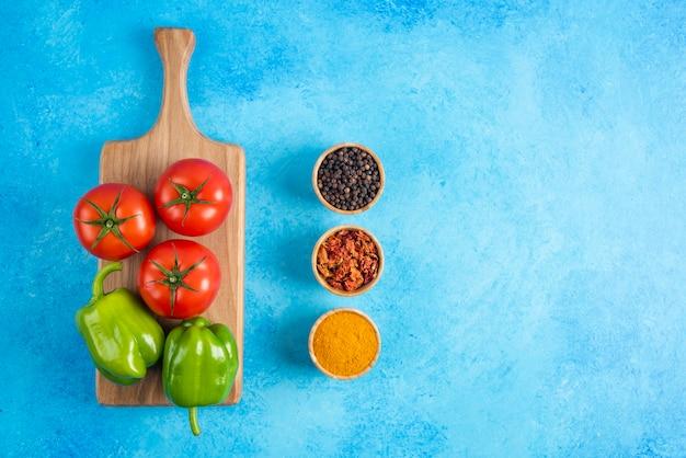 木の板の上の野菜と青いテーブルの上のスパイスの平面図です。