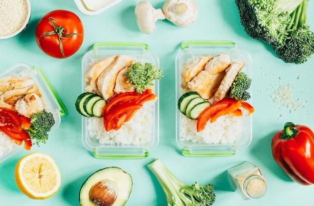 薄緑色の背景にプラスチック製のボウルに野菜、米、肉の上面図
