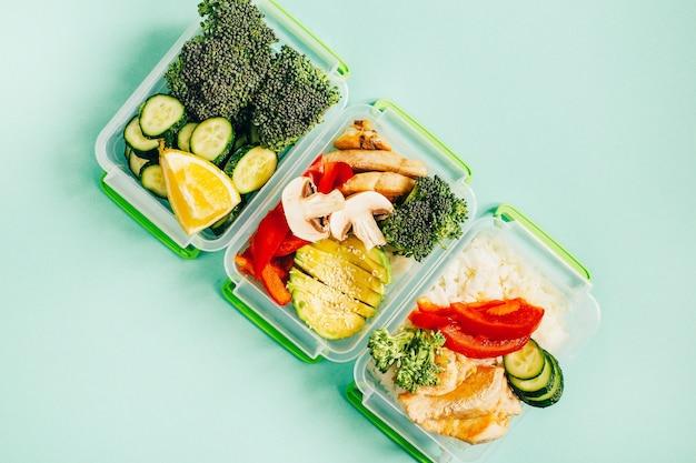 밝은 녹색 표면에 플라스틱 그릇에 야채, 쌀, 고기의 평면도