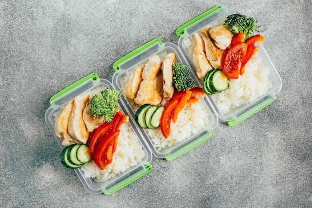ライトグレーの背景にプラスチック製のボウルに野菜、米、肉の上面図