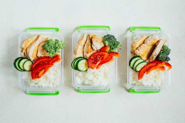 밝은 흰색 표면에 플라스틱 그릇에 야채, 쌀, 고기의 평면도
