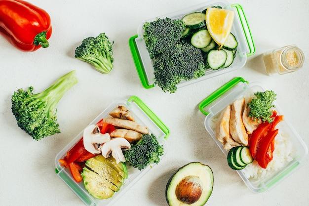明るい白い表面のプラスチック製のボウルに野菜、米、肉の上面図