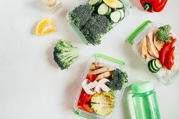白い表面のプラスチック製のボウルに野菜、米、肉の上面図