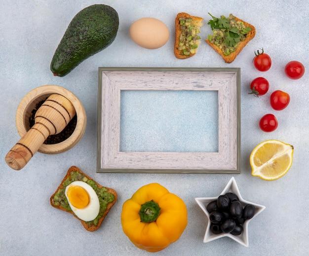 Вид сверху овощей, таких как авокадо, лимон, черные маслины, помидоры, желтый перец и ломтик хлеба с мякотью авокадо на белой поверхности.