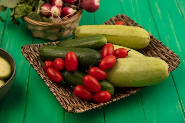Вид сверху на овощи, такие как сливы, помидоры, огурцы и цуккини, на плетеном подносе с редисом на ведре на зеленой деревянной стене