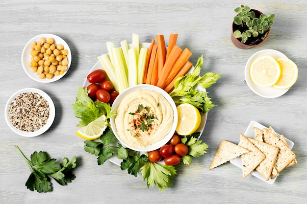 Вид сверху овощей с хумусом и крекерами