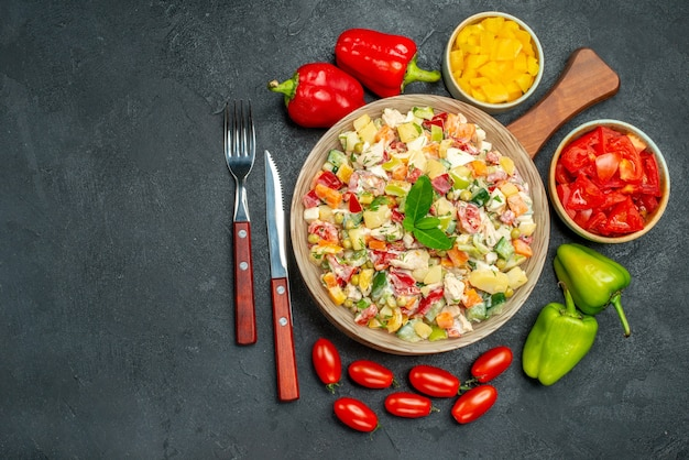 濃い灰色の背景にあなたのテキストのための自由な場所と側面にカトラリーと野菜の野菜サラダの上面図