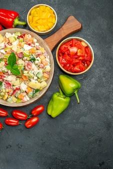어두운 회색 배경에 오른쪽 하단에 텍스트를위한 무료 장소가있는 측면에 칼과 야채가 들어간 야채 샐러드의 상위 뷰