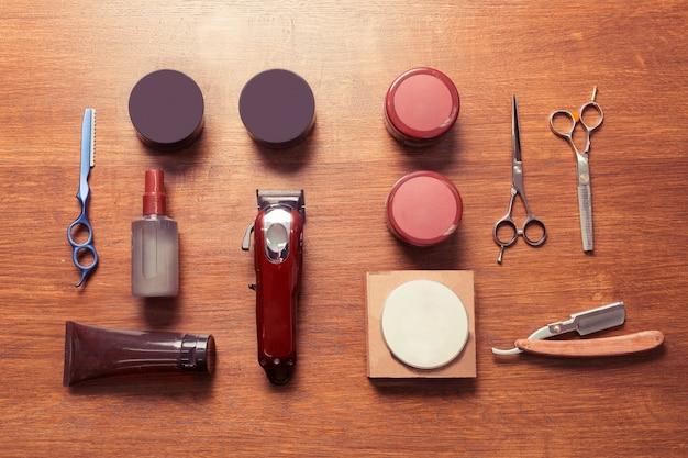 木製の背景、フラットレイオーバーヘッドビューのヴィンテージ理髪店ツールの上面図 Premium写真