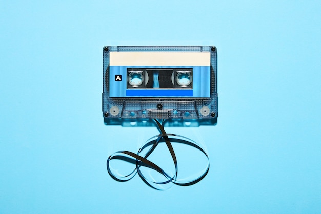 青にもつれたテープとヴィンテージの昔ながらのプラスチック製コンパクトオーディオカセットの上面図