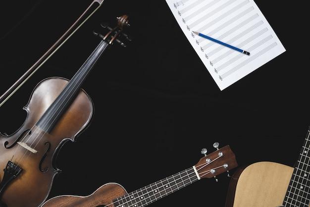 Вид сверху скрипки гитары и гавайской гитары с листом музыкальной ноты на черном фоне