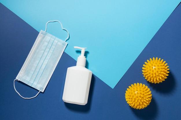 Вид сверху на вирусы с медицинской маской и бутылкой с жидким мылом