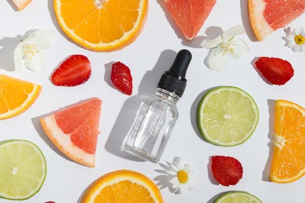흰색 배경에 있는 비타민 c 점적기, 혈청, 화장품 오일 및 오렌지, 라임, 자몽 조각의 상위 뷰