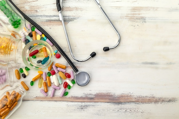 Вид сверху витаминных таблеток и стетоскопа